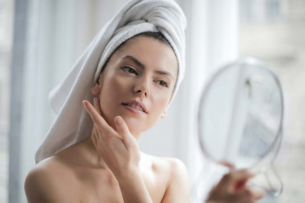 A woman feeling her youthful skin after anti-wrinkle injectables and cosmetic fillers treatment