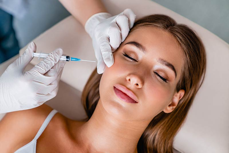 A cosmetic specialist administering cosmetic injectables to a woman during a cosmetic skin treatment with skin doctor