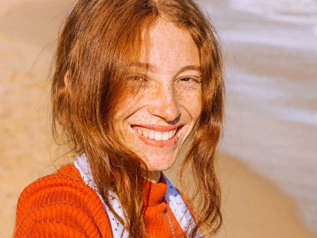 A smiling woman in a beach with many face freckles is in a high risk for melanoma, a type of skin cancer