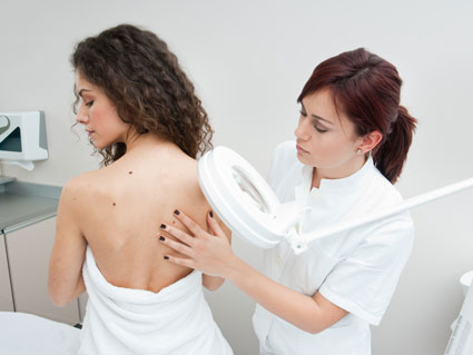 Dermatologist doctor inspecting woman skin for moles and melanoma
